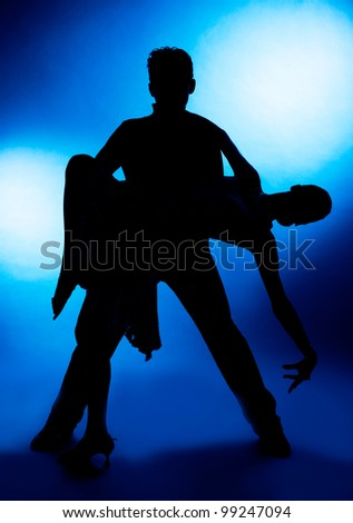 A silhouette of a couple dancing, against blue studio background