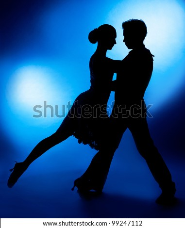 A silhouette of a couple dancing against blue studio background