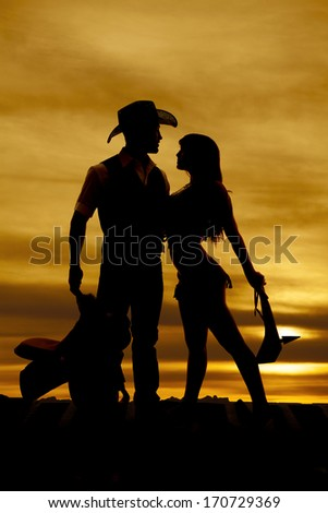 A silhouette of a cowboy and an indian in front of a sunset.