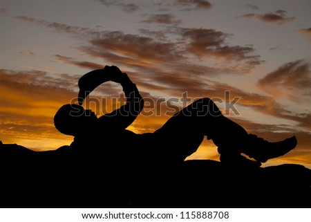 a silhouette of a  cowboy laying down on the ground with a beautiful sky behind him.