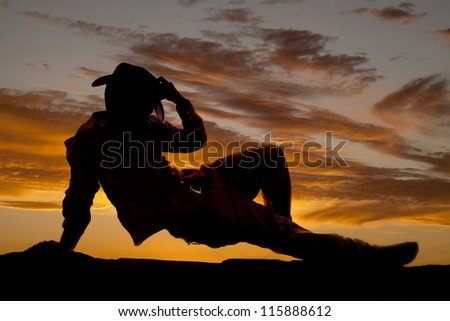 A silhouette of a cowboy pushing up off the ground with his arm and holding on to his hat.