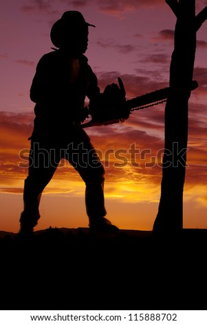 a silhouette of a cowboy with a chainsaw cutting a tree down