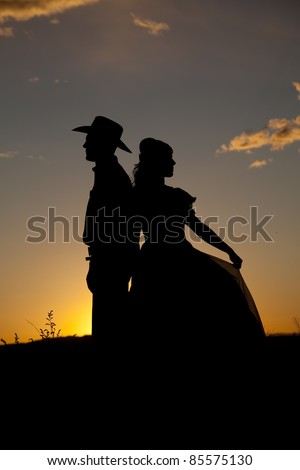 A silhouette of a cowboy with his back to a woman in the sunset.