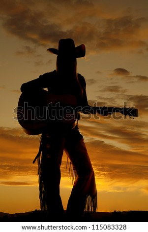 A silhouette of a cowgirl playing her guitar. - stock photo