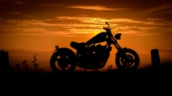 A silhouette of a custom made chopper against a colourful sunset, England, UK