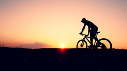 A silhouette of a cyclist practicing a bicycle on a mountain