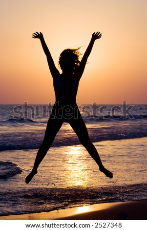 A silhouette of a happy woman jumping