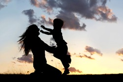 a silhouette of a happy young boy child running into the arms of his loving mother for a hug, in front of the sunset in the sky on a summer day.