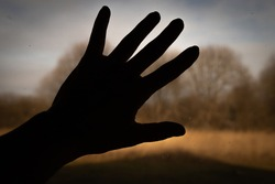 A silhouette of a human hand palm on a dirty window glass with blurred outside landscape. A touch of presence.
