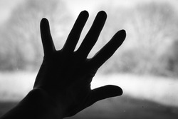 A silhouette of a human hand palm on a dirty window glass with blurred outside landscape. A touch of presence. Black and white.