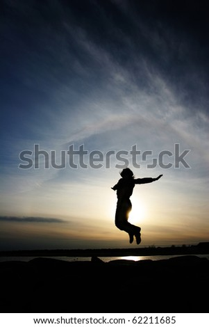 A silhouette of a jumping woman on  sunset background