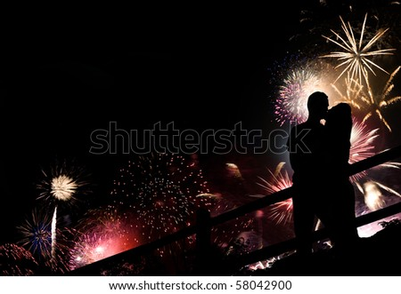 A silhouette of a kissing couple in front of a huge fireworks display.