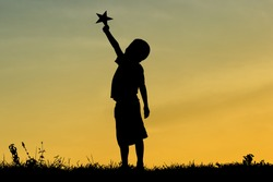 A silhouette of a little child reaching out to grab stars, Expresses the ambition, The joy of a small child with dreams. Kid having fun at sunset. Summer vacation and travel concept.