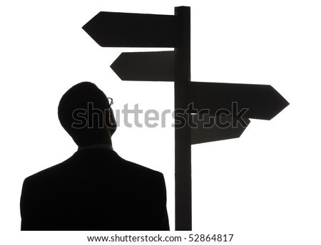 A silhouette of a lost man choosing his destination from the directing boards.