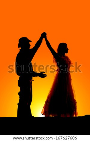 A silhouette of a man and woman dancing in the outdoors.