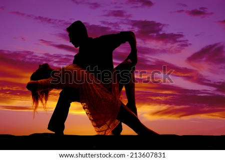A silhouette of a man and woman dancing she is leaning back over his knee.
