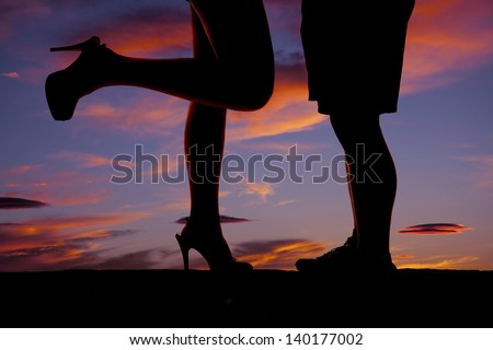 A silhouette of a man and woman's legs.