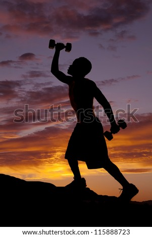 A silhouette of a man climbing up a hill working out with weights.