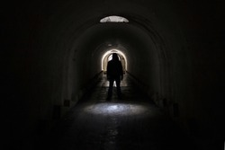 A silhouette of a man in dark clothes with a hood going to the exit to the lighted door from a dark terrible underground passage lit through a hatch in the ceiling.