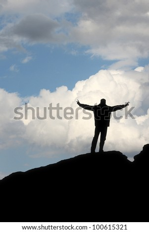 A silhouette of a man in front of the blue sky making a winner pose - stock photo