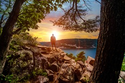 A silhouette of a man looking out into the sunset over Devils Lake State Park from a hiking viewpoint in Baraboo, Wisconsin USA.