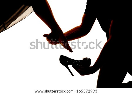 A silhouette of a man placing on a woman's shoe.