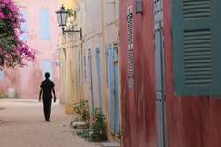A silhouette of a man walking in a small colored street of Goree island in Senegal