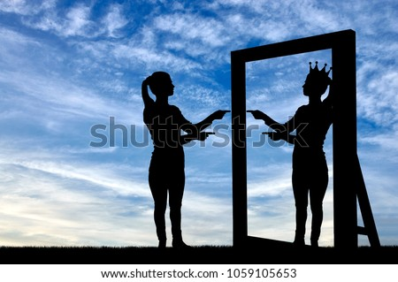 A silhouette of a narcissistic woman raises her self-esteem in front of a mirror. The concept of narcissism and selfishness Foto stock ©