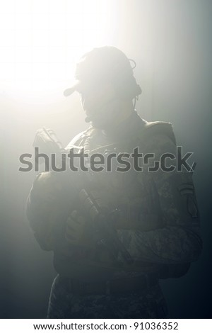 A silhouette of a soldier in the smoke after the explosion