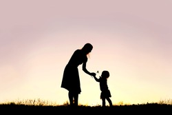 A silhouette of a sweet toddler girl is handing her mother a Daisy flower, in a meadow outside at sunset on a summer day.