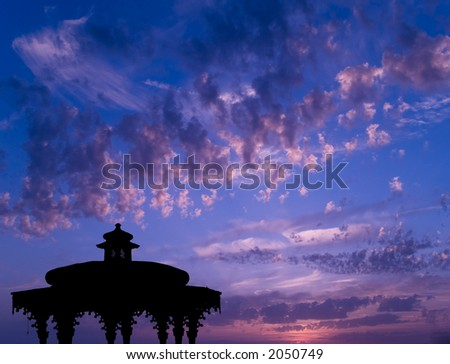 A silhouette of a temple at sunset.