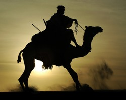 A silhouette of a Tuareg rider and camel rising after mounting in the desert