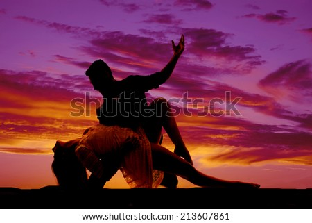 A silhouette of a woman and man doing a dance move in the outdoors.