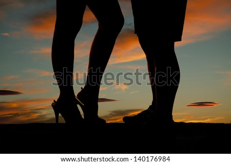 A silhouette of a woman and man's legs with a beautiful sky behind them
