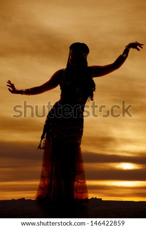 a silhouette of a woman belly dancing in the beautiful sunset