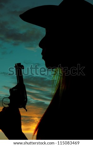 A silhouette of a woman blowing on the tip of her gun.