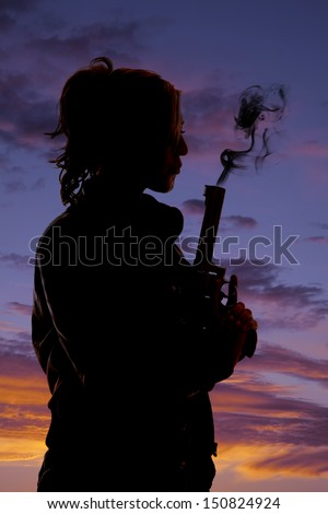 A silhouette of a woman blowing the smoke off  her pistol.