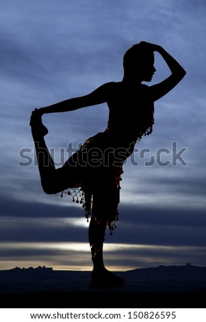 A silhouette of a woman dancing and holding her foot with a blue sunset in the background