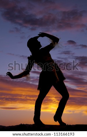 A silhouette of a woman dancing in the sunset.