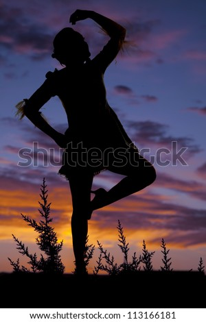 A silhouette of a woman dancing with a colorful sky behind her.