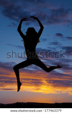 a silhouette of a woman doing a dance leap.