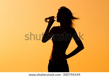 A silhouette of a woman drinking water.Refreshment