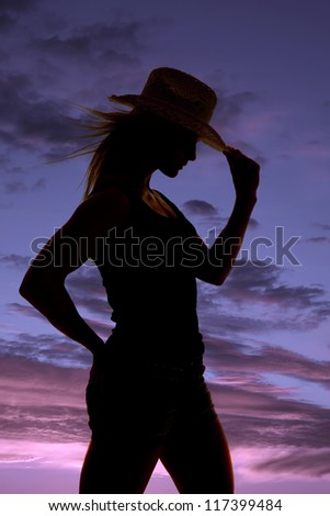 A silhouette of a woman holding on to the brim of her hat.