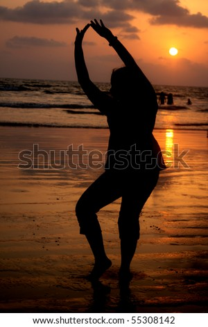 A silhouette of a woman in a traditional Indian Classical dance pose, on a beach at sunset.