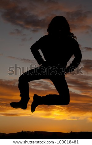 A silhouette of a woman jumping up in the colorful sky.