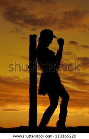 A silhouette of a woman leaning back against a post touching the brim of her hat.