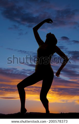 A silhouette of a woman leaning back and dancing in the outdoors.