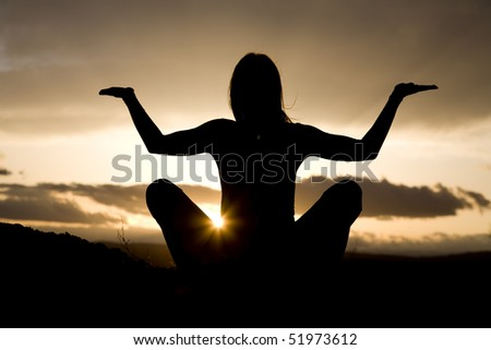 A silhouette of a woman relaxing doing a yoga pose meditating in the outdoors with a beautiful sunrise.