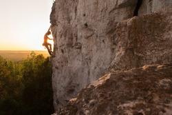 A Silhouette of a Woman rock climbing on Ontario's Niagara Escarpment in Canada