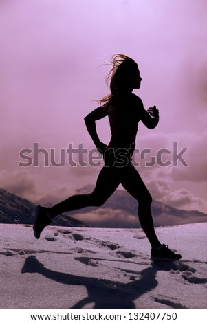 A silhouette of a woman running in the snow up in the mountains.